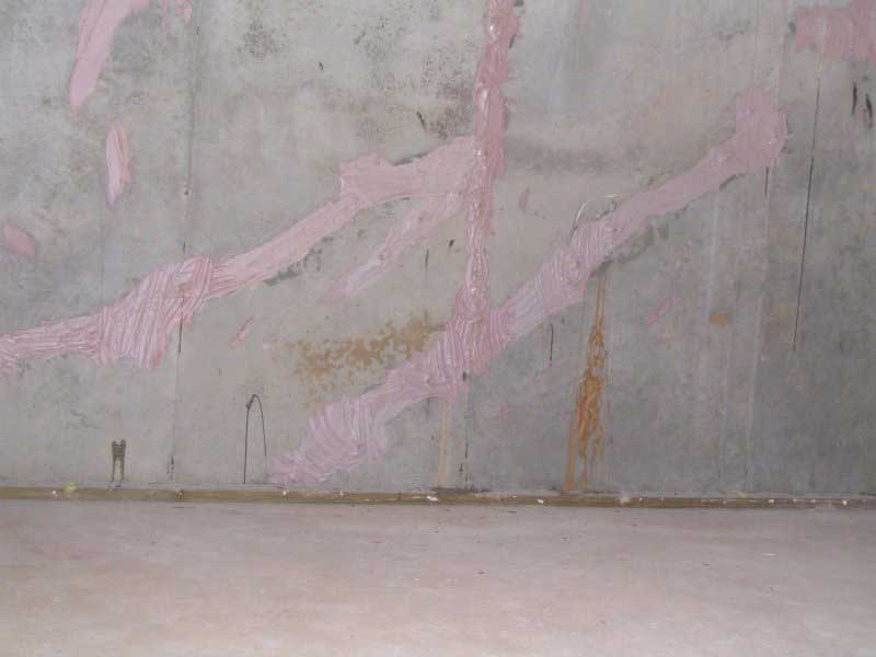 Epoxy injections inside cracks on a poured concrete wall